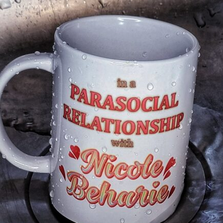 """White, glossy ceramic mug with graphic, 15 oz. ceramic mug sitting in a sink. Typography around image reads, """"in a parasocial relationship with Nicole Beharie"""""""